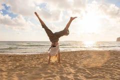 Cartwheel de giro da mulher feliz livre que aprecia o por do sol em Sandy Beach Fotos de Stock