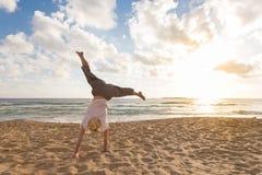 Cartwheel de giro da mulher feliz livre que aprecia o por do sol em Sandy Beach Fotografia de Stock Royalty Free