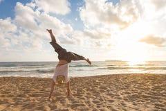 Cartwheel de giro da mulher feliz livre que aprecia o por do sol em Sandy Beach Imagens de Stock