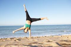 Cartwheel de giro da mulher nova na praia foto de stock royalty free