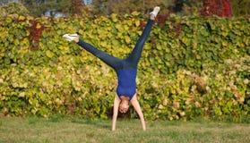 Cartwheel desportivo da mostra da mulher fotografia de stock