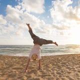 Cartwheel felice libero di tornitura della donna che gode del tramonto su Sandy Beach Fotografie Stock Libere da Diritti