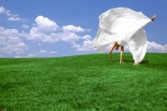 Cartwheel in the Summertime. Green grass and blue sky background with Woman Flipping Feeling Happy and Free doing a Somersault Stock Photos