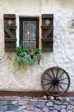 Cartwheel at the window with shutters Royalty Free Stock Photos