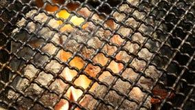 carvão 4K ardente feche acima dos carvões encarnados incandesceu no fogão sob a grade do BBQ e carvões de incandescência filme