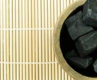Carvão vegetal de bambu no tubo de bambu na esteira de bambu Imagem de Stock