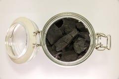 Carvão vegetal preto no frasco de vidro Imagem de Stock
