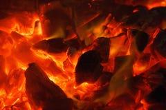 Carvões amassados quentes de incandescência do carvão vegetal perto acima da textura do fundo bonfire foto de stock