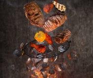 Carvões amassados quentes, grelha do ferro fundido e carnes saborosos voando no ar imagens de stock royalty free