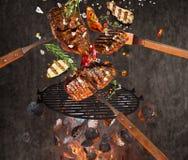 Carvões amassados quentes, grelha do ferro fundido e carnes saborosos voando no ar foto de stock