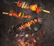 Carvões amassados quentes, grelha do ferro fundido e espetos saborosos voando no ar foto de stock royalty free