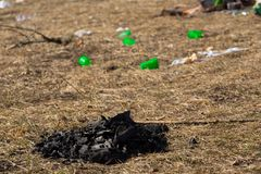 Carvões da fogueira na grama da mola nas montanhas deixadas por turistas no fundo do lixo dispersado e de copos plásticos imagem de stock