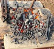 Carvões e ferramentas do ferreiro imagem de stock