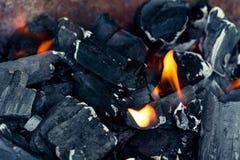 Carvões pretos e chama alaranjada - um fogo fotos de stock