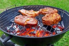 Carvões vegetais encarnados e bifes na grade do carvão vegetal foto de stock royalty free
