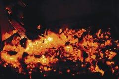 Carvões vermelhos quentes da lenha em uma chaminé em um fundo preto imagem de stock royalty free