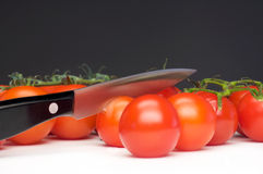 Carve a tomato. Black knife cuts a tomato in two parts Royalty Free Stock Image