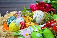 Carved绘了与其他装饰品盛大宴餐的白色复活节彩蛋 免版税库存照片