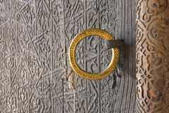 Carved antique door with a gold ring. / Vintage Oriental patterns Stock Photography