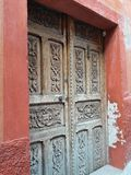 Carved Antique Wooden Door and Rustic Mexican Stucco Doorway with Brown and Rust Textured Wall Background Stock Photo