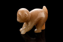 Carved aragonite monkey. Hand carved brown aragonite monkey statuette on black background Stock Photo