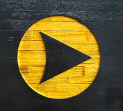 Carved arrow sign on wood. Painted black and yellow Royalty Free Stock Photo
