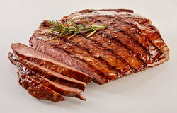 Carved barbecued medium-rare flank steak. Carved barbecued medium-rare flank beef steak cut through to show the juicy texture garnished with a sprig of fresh royalty free stock images