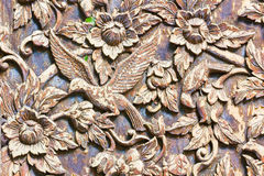 Carved bird and flowers on the wood background Royalty Free Stock Image