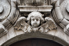 A Carved Cherub in Bruges Belgium. A black and white close up shot of a vintage carved cherub statue in an historic building in Bruges, Belgium Stock Photography