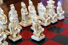 Carved chess pieces in chinese style on a chessboard. Royalty Free Stock Photos