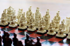 Carved chess pieces in chinese style on a chessboard. Royalty Free Stock Image
