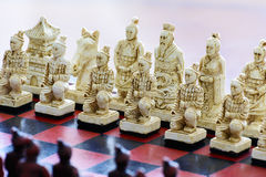 Carved chess pieces in chinese style on a chessboard. Royalty Free Stock Photography