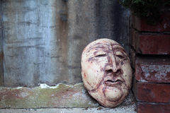 Carved Clay Face Leaning Against a Red Brick Wall Stock Photo