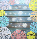 Carved colorful paper snowflakes on a blue wooden background Royalty Free Stock Photography