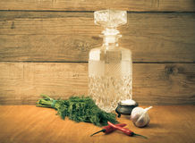 Carved decanter of vodka and ingredients for tinctures. Tinted Stock Photo