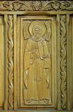 Carved detail of St Anthony on wooden door on Old Court Church,, Bucharest, Romania. Wooden door with carved representation of Saint Anthony on church bearing royalty free stock photos