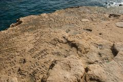 Carved and engraved names in the rock. SAINT PETER`S POOL, MALTA - AUGUST 21, 2017: People carving and engraving their names and initials in the rocks at Saint Royalty Free Stock Photos