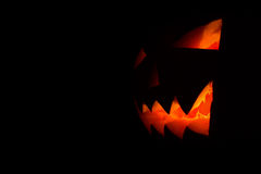 Carved face of pumpkin glowing on Halloween black background Stock Photography