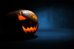 The carved face of pumpkin glowing on Halloween on blue background Stock Image