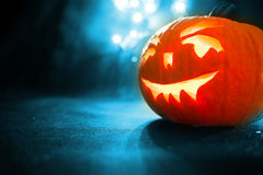 Carved face of pumpkin glowing on Halloween on blue bokeh light background Stock Photography
