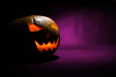 The carved face of pumpkin glowing on Halloween on purple background Stock Photos