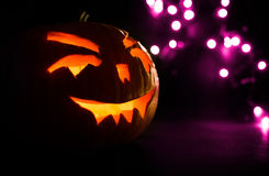 Carved face of pumpkin glowing on Halloween on purple bokeh light background Royalty Free Stock Images