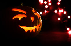 Carved face of pumpkin glowing on Halloween on red bokeh light background Royalty Free Stock Photos