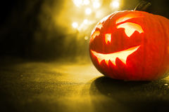 Carved face of pumpkin glowing on Halloween on yellow bokeh light background Stock Photography