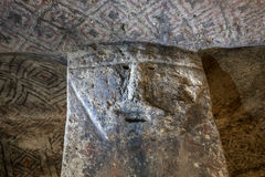 Carved face in rock in underground grave Royalty Free Stock Photo