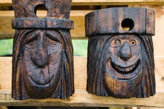 Carved Faces Birdhouses. Two smiling wooden faces carved by chainsaw form birdhouses stock photo