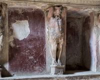 Carved figure and niche where bath supplies stored in bathhouse remains, Scavi Di Pompei. Pictured is a carved figure and niches where bath supplies were stored Stock Photography