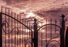 Carved forjou a cerca do metal contra o escarlate vermelho do por do sol fotografia de stock royalty free