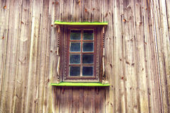 Carved frame and window in the old wooden house from boards Stock Image