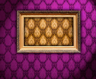 Carved Gilded Frame on Violet Wallpaper. A carved gilded vintage frame on vilet wallpaper Royalty Free Stock Photos
